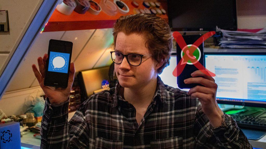 Stach houdt twee telefoons vast. Op de linkertelefoon is een Signal-logo afgebeeld. Op de rechtertelefoon een WhatsApp-logo. Door het WhatsApp-logo staat een rood kruis.