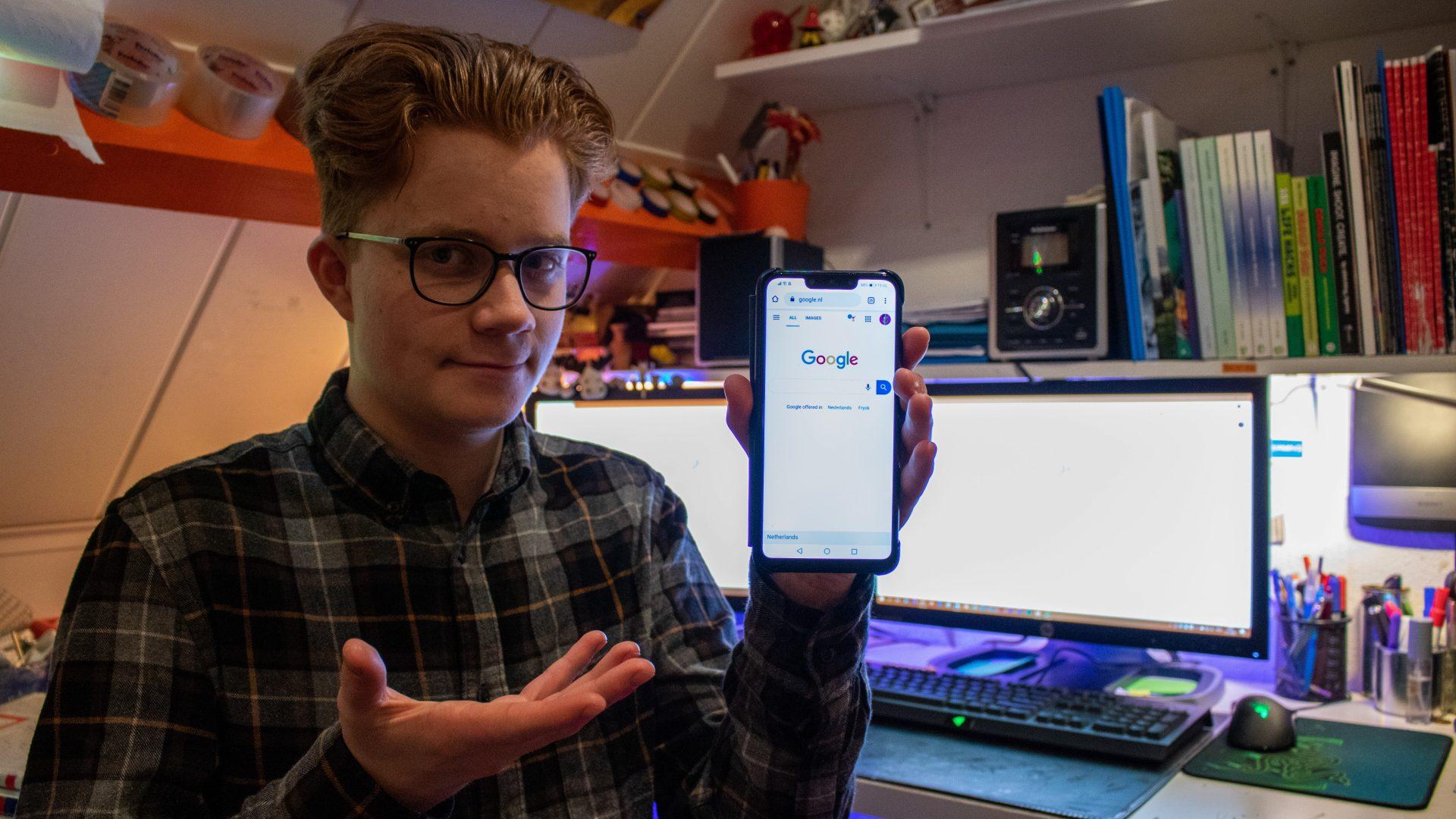 Stach Redeker houdt een telefoon vast. Op het scherm is de zoekmachine 'Google' te zien.