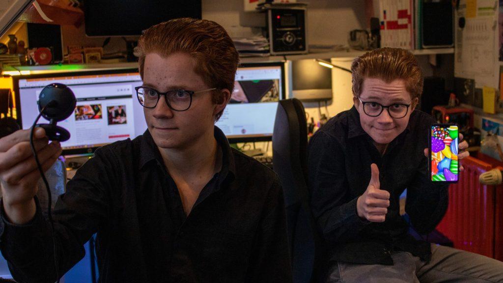 Op de foto zijn twee Stachs zichtbaar. De eerste Stach kijkt levenloos in een webcam; de tweede Stach houdt een telefoon met Candy Crush vast.
