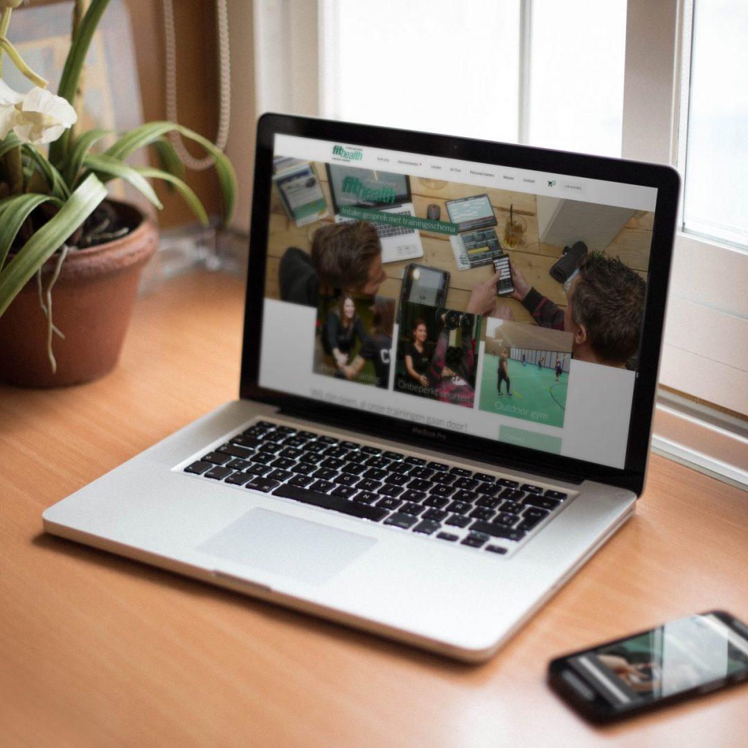 De Fithealth-website is geprojecteerd op een MacBook